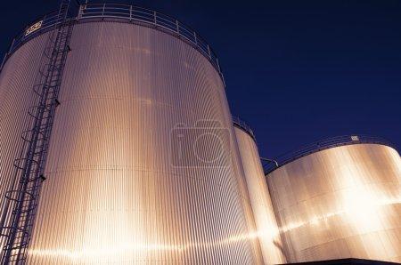 Photo pour Grands réservoirs de stockage de carburant, industriels au coucher du soleil - image libre de droit