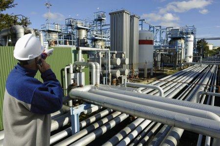 Photo pour Travailleur pétrolier pointant sur la construction de longs pipelines, détail intérieur raffinerie - image libre de droit
