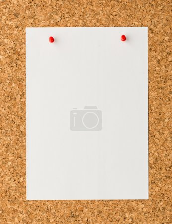 White paper note sheet with red push pin on cork board