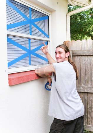Photo pour Young man pointing to windows he has taped up to prepare for a hurricane. - image libre de droit