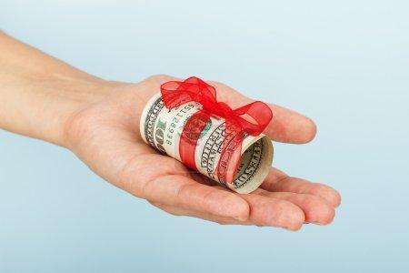 Photo pour Main de femme tient de l'argent sur le fond bleu.. billets de dollar - image libre de droit