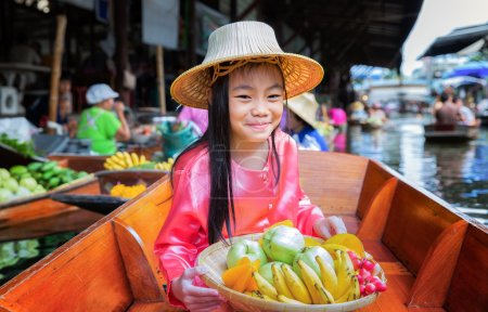 Photo for Child sit on the boat and hold the fruit basket in Traditional floating market , Thailand. - Royalty Free Image