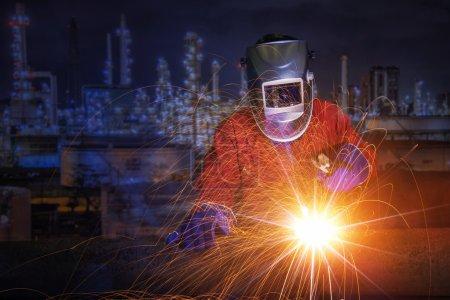 Photo pour Travailleur avec masque de protection soudure métal et étincelles dans l'usine de raffinage de pétrole . - image libre de droit