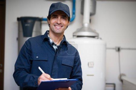 Photo pour Ouvrier Technicien maintenance un réchauffeur d'eau chaude - image libre de droit