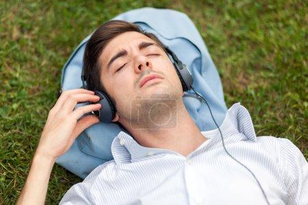 Photo pour Jeune homme écoutant de la musique sur l'herbe - image libre de droit