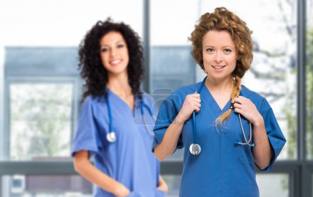 Nurses with stethoscopes looking at camera