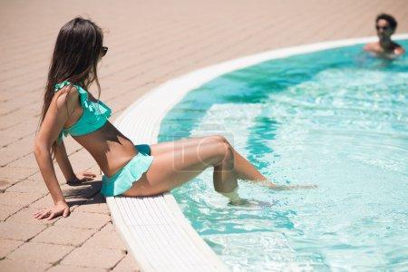 Woman refreshing feet on poolside