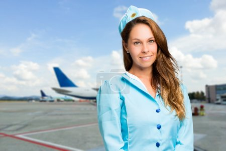 Smiling hostess with airplane