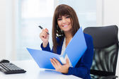 businesswoman holding folder while sitting at office