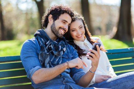 couple using smartphone while sitting on bench