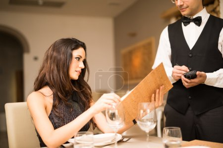 Photo for Woman ordering dinner in a luxury restaurant - Royalty Free Image