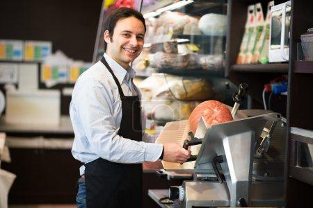 Shopkeeper cutting Italian sliced meat