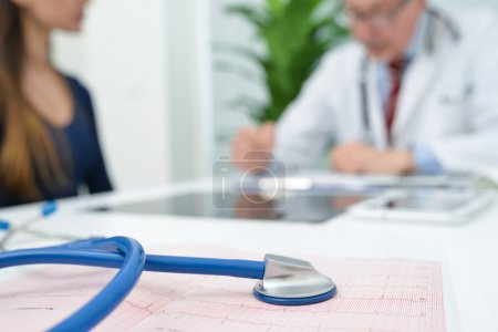 Photo for Stethoscope on an electrocardiogram, very shallow depth of field. Doctor and patient in the background - Royalty Free Image