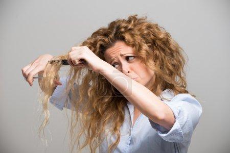 Photo pour Femme coupant ses propres cheveux - image libre de droit