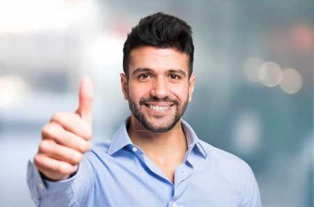 Photo pour Portrait d'un homme d'affaires souriant abandonnant les pouces - image libre de droit