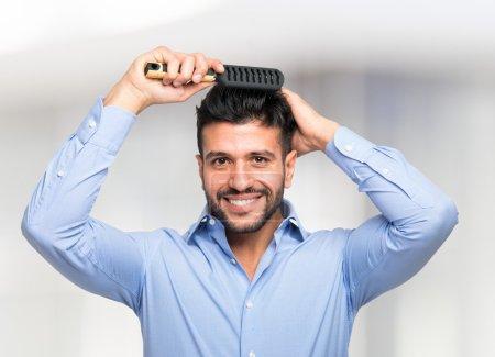 Photo pour Heureux homme peignant ses cheveux - image libre de droit
