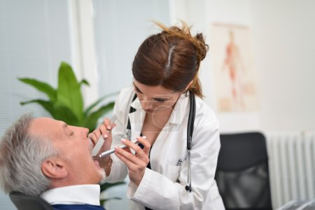 Doctor checking a patient's throat