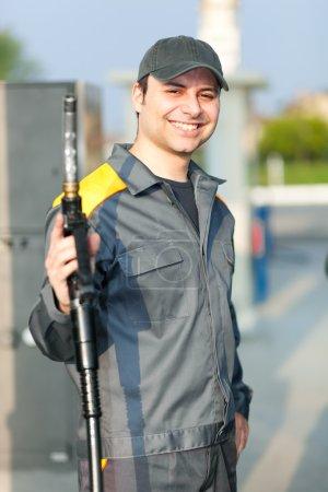 Photo pour Travailleur souriant à la station-service - image libre de droit