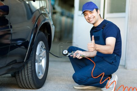 Smiling mechanic inflating tire