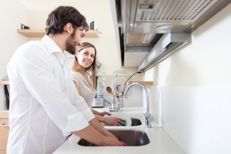 Photo for Young couple doing dishes in the kitchen - Royalty Free Image