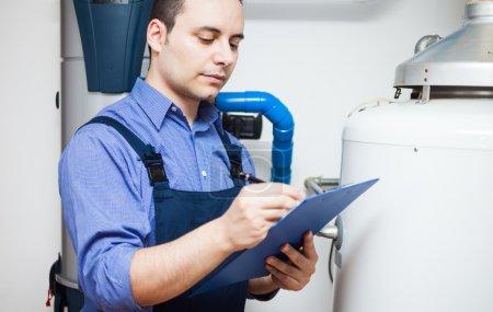 Photo pour Technicien d'entretien d'un chauffe-eau - image libre de droit