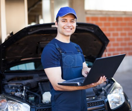 Photo for Smiling mechanic using a laptop computer to check a car engine - Royalty Free Image