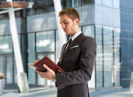 Businessman taking notes on agenda