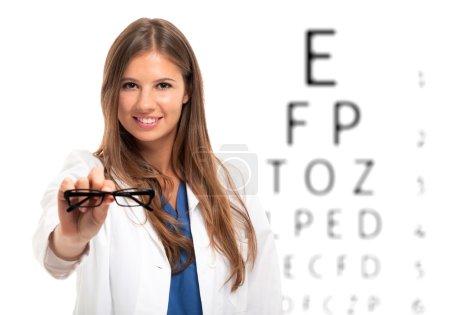 Oculist holding pair of eyeglasses