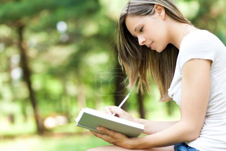 Young woman studying at park