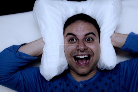 Photo for Insomniac man using a pillow to cover his ears - Royalty Free Image