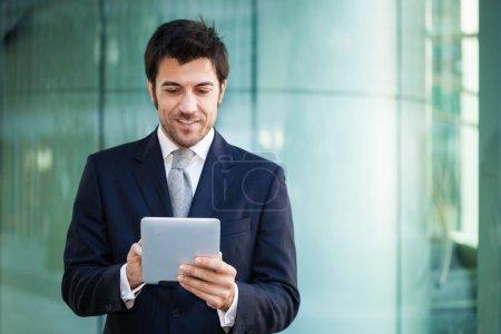 Photo pour Homme d'affaires souriant à l'aide de son ordinateur tablette - image libre de droit