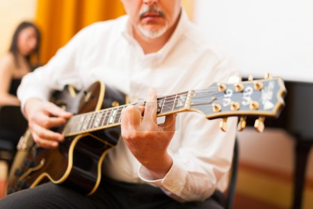 Photo for Guitarist playing an archtop guitar - Royalty Free Image