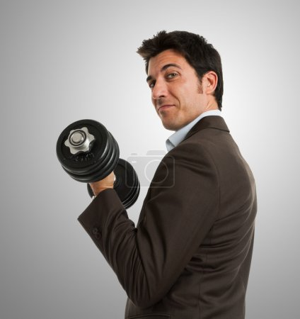 Businessman lifting a dumbbell