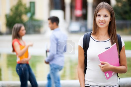 Photo for Outdoor portrait of a smiling student in front of her school - Royalty Free Image