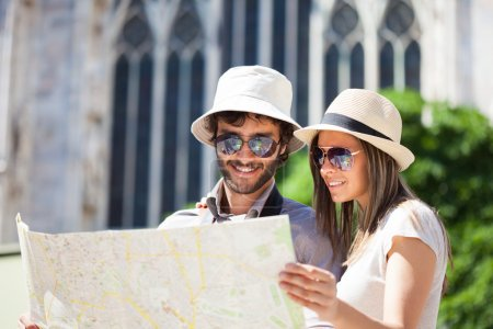 Photo for Happy couple of tourists holding map - Royalty Free Image