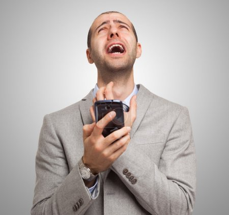 Photo for Portrait of a desperate man holding his mobile phone - Royalty Free Image