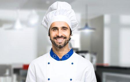 Photo pour Portrait d'un chef souriant dans la cuisine - image libre de droit