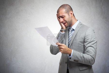 Photo pour Homme déprimé lisant un document - image libre de droit