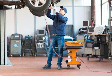 Photo pour Mécanicien en vissant un pneu avec une clé pneumatique - image libre de droit