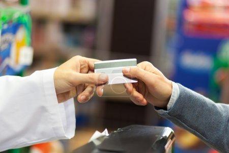 Storekeeper taking credit card from customer