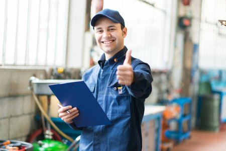 Photo for Portrait of a worker in a factory showing thumbs up - Royalty Free Image