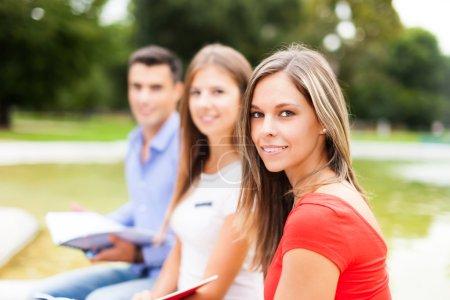 Photo pour Portrait extérieur de trois élèves qui étudient dans un parc - image libre de droit