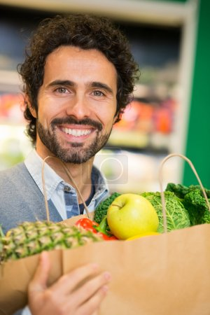 Photo for Smiling man shopping in a supermarket - Royalty Free Image