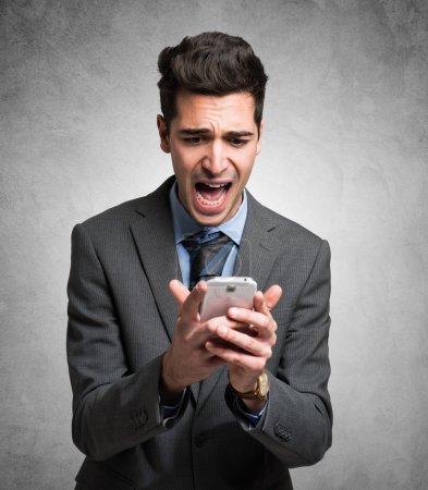 Foto de Retrato de un hombre desesperado sosteniendo su teléfono móvil - Imagen libre de derechos