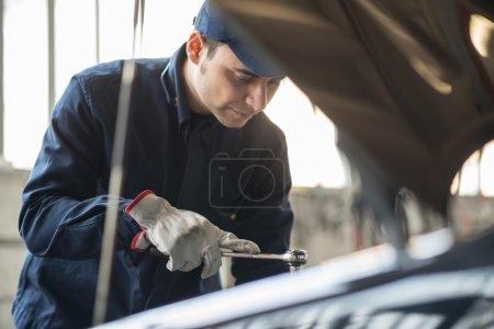Auto mechanic at work on car