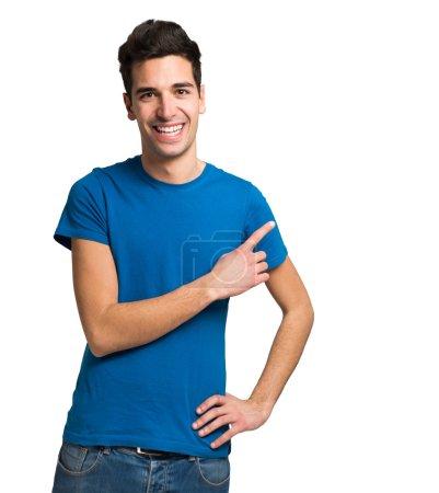 Photo pour Jeune homme souriant pointant son doigt vers le copyspace - image libre de droit