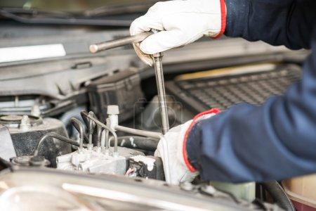 Mechanic working on car engine
