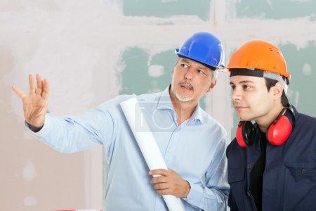Architect explaining work to foreman