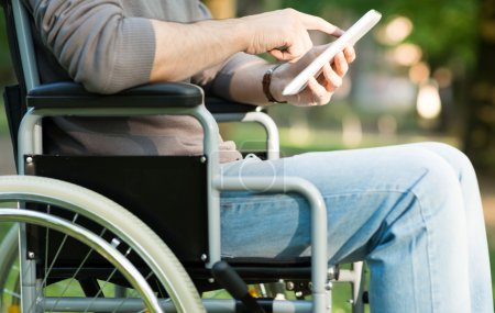 Man using tablet in wheelchair