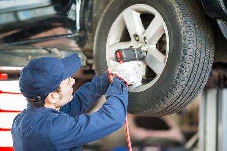 Mechanic replacing a wheel